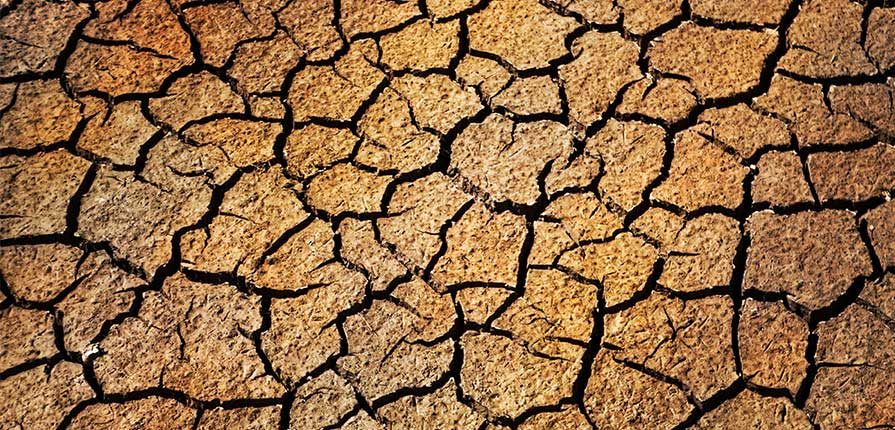 A photo of dry, cracked ground illustrates the process that happens with some Los Angeles slab leaks.